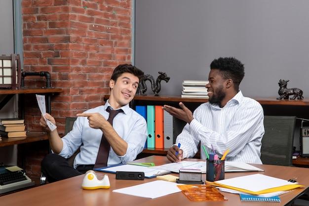 전면 보기 비즈니스 협상 두 사업가가 서로 이야기하는 동안 그들 중 한 명이 종이를 가리키고 있습니다