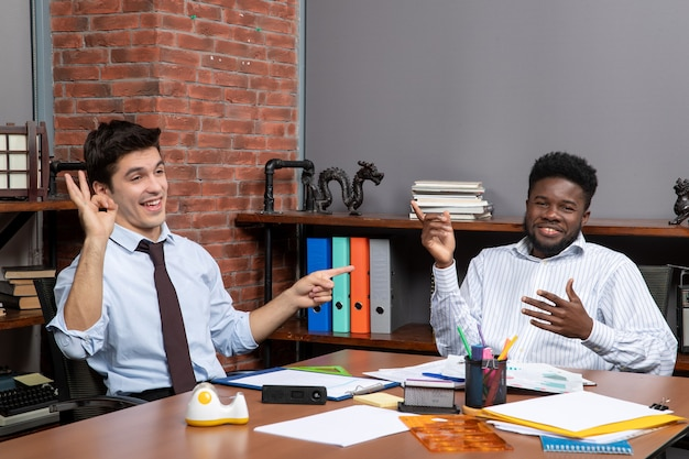 Trattative commerciali vista frontale due manager aziendali soddisfatti al lavoro in ufficio