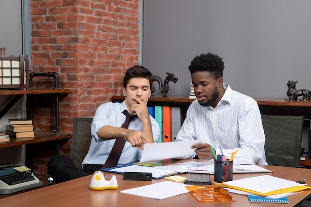 전면 보기 비즈니스 협상 두 명의 동료가 책상에 앉아 프로젝트에 대해 이야기합니다.