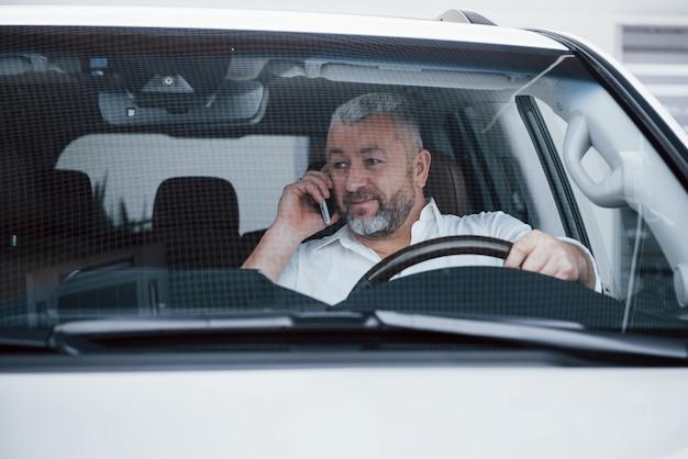 正面図。停車中の車内での商談。会話-新しい取引について