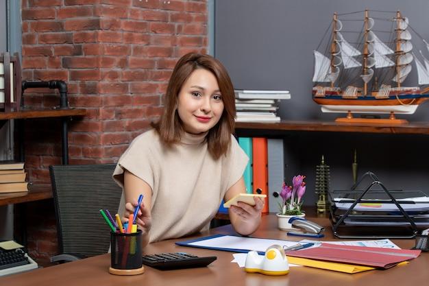 オフィスの机に座ってペンを取る正面図ビジネス女性