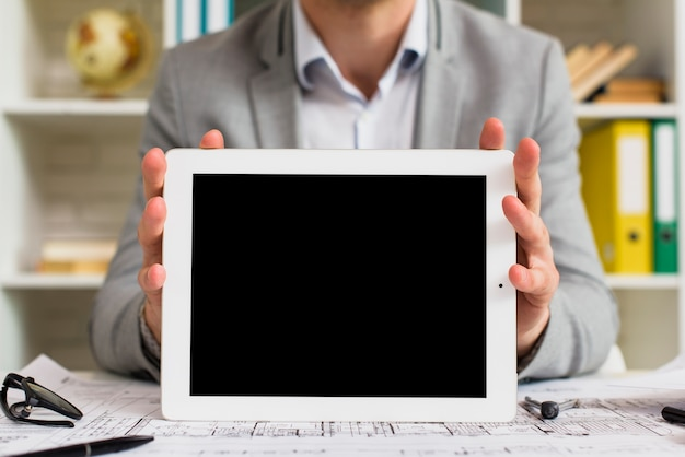 Front view businessman holding tablet mock-up