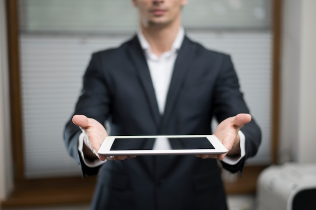 Front view of businessman holding tablet