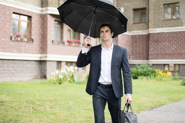 Front view of businessman holding umbrella