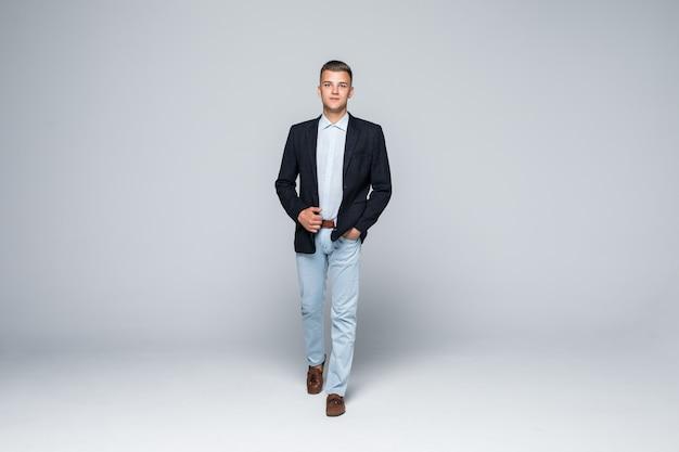 Vista frontale dell'uomo d'affari in giacca e jeans si muove attraverso lo studio isolato su bianco