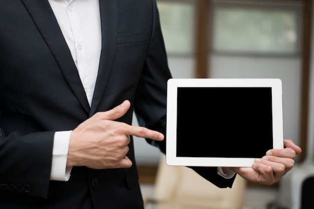 Front view of businessman pointing at tablet