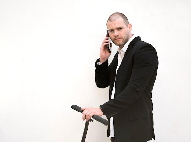 Uomo d'affari di vista frontale che parla sul telefono