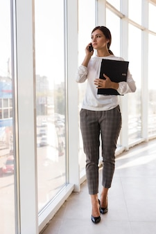 Front view of businesswoman holding binder and talking on the phone