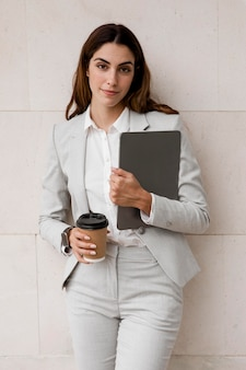 Front view of businesswoman holding tablet and coffee cup