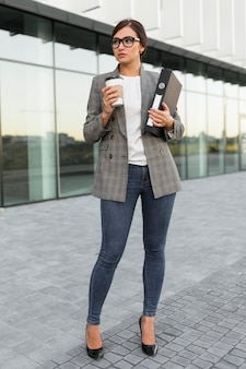 Front view of businesswoman posing outdoors with coffee and binder