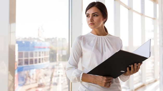 Front view of businesswoman posing with binder