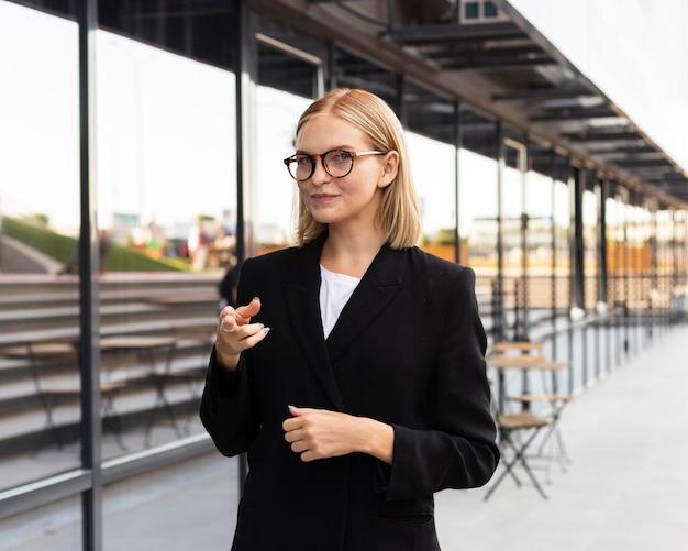 Vista frontale della donna di affari utilizzando il linguaggio dei segni all'aperto al lavoro