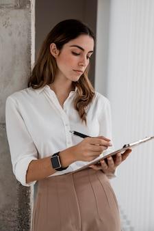 Vista frontale della donna di affari con i appunti
