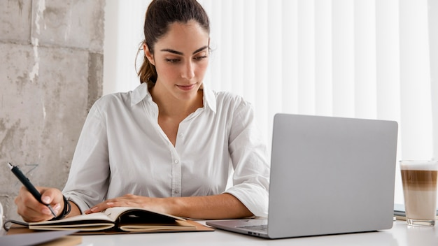 Front view of businesswoman working with laptop and notebook