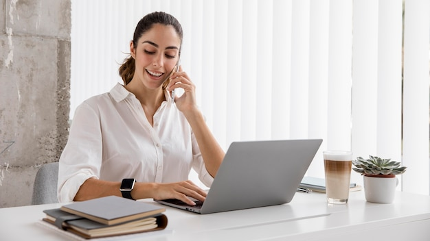 Front view of businesswoman working with smartphone and laptop