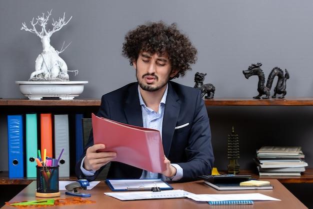 彼のオフィスでファイルを保持している机に座っている忙しいビジネスマンの正面図