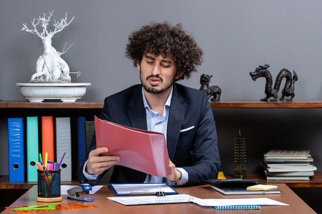 Front view busy businessman sitting at the desk holding files in his office