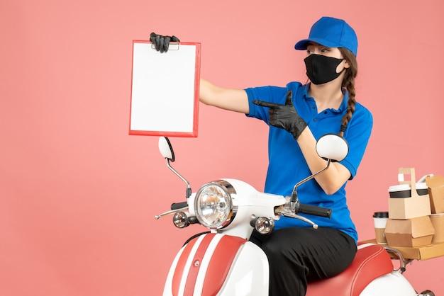 Vista frontale della donna del corriere impegnata che indossa maschera medica e guanti seduta su uno scooter con in mano fogli di carta vuoti che consegnano ordini su sfondo color pesca pastello