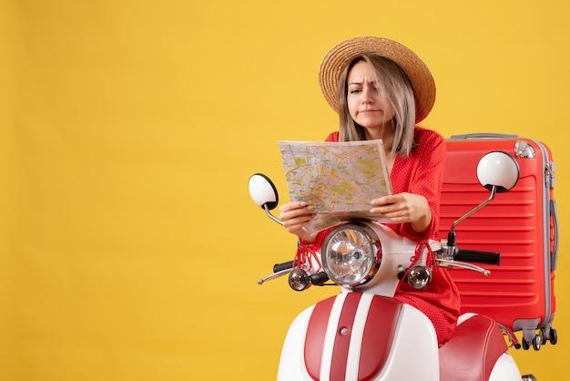 Vista frontale della ragazza graziosa occupata sul ciclomotore con la valigia rossa che esamina la mappa