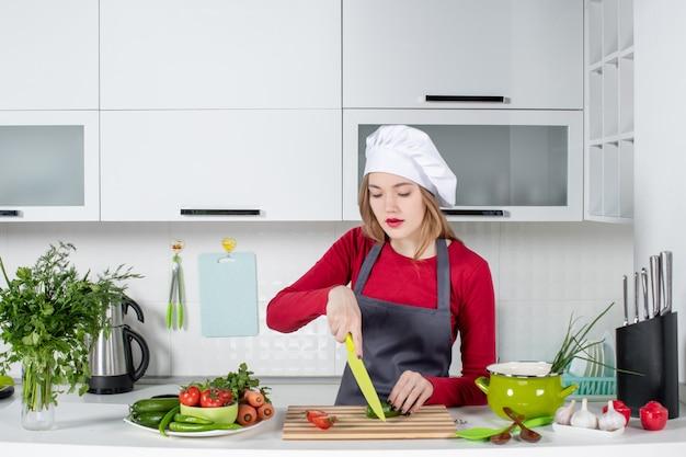 Vista frontale donna impegnata in grembiule che taglia cetriolo