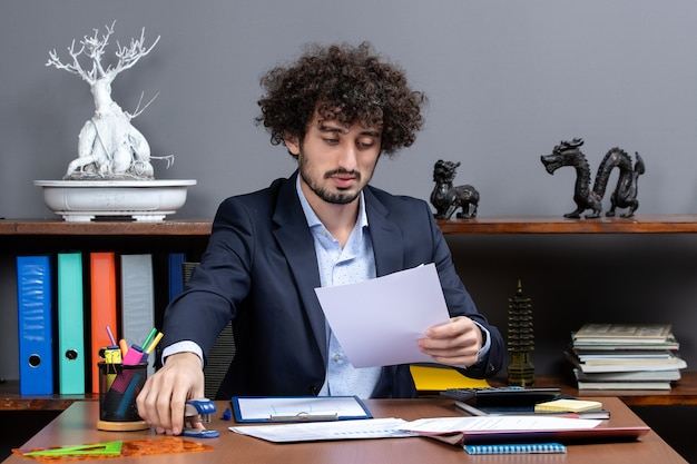 Front view busy young businessman sitting at desk holding stapler