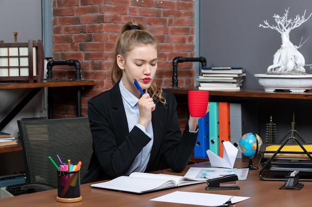 Vista frontale di una giovane donna impegnata seduta a un tavolo e con in mano una tazza rossa che legge un documento di fronte a lei in ufficio
