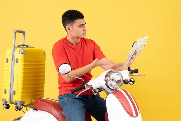 Vista frontale occupato giovane uomo sul ciclomotore guardando la mappa