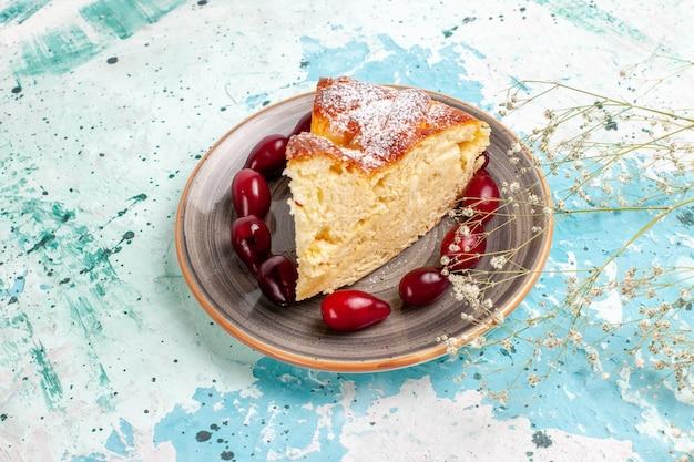 青い机の上に新鮮な赤いハナミズキと正面図のケーキスライス