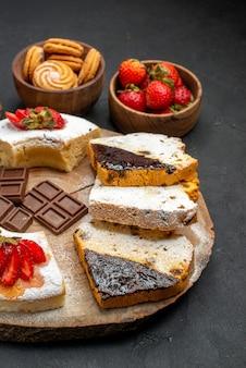 Кусочки торта с печеньем и фруктами на темном фоне, вид спереди