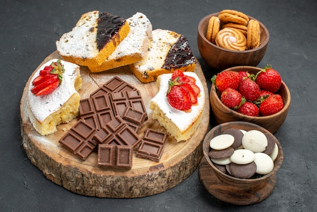 暗い背景にフルーツクッキーとチョコバーと正面のケーキのスライス