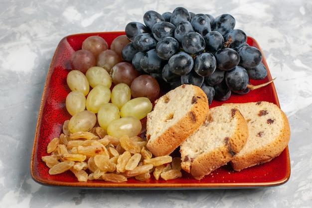 Fette di torta vista frontale con uva e uvetta all'interno del piatto rosso su superficie bianca