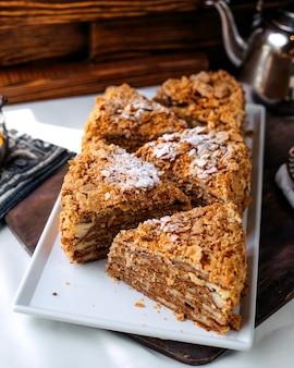 Торт спереди сладкий вкусный вкусный нарезанный внутри белой тарелке на коричневой поверхности