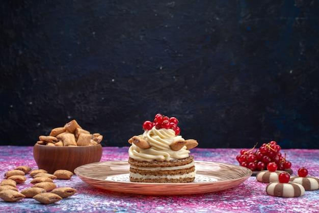Vista frontale della torta con crema insieme a biscotti e mirtilli rossi sulla superficie scura