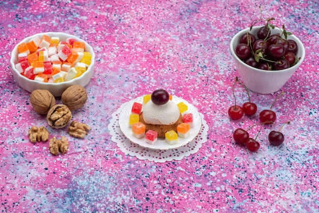 Front view of cakes and cherries along with walnuts and marmalades on the colored surface