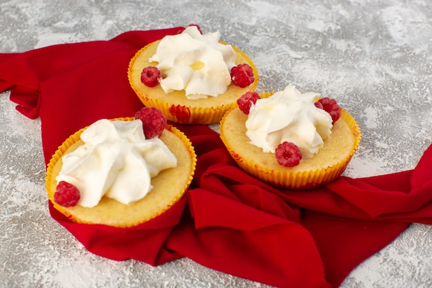 Front view of cakes with cream yummy designed with raspberries and cream