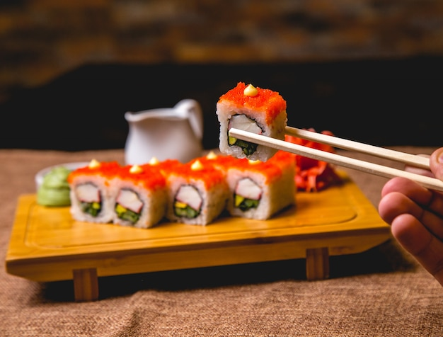 Front view california sushi rolls with wassabi and ginger on a board a male hand holds a roll of chopsticks