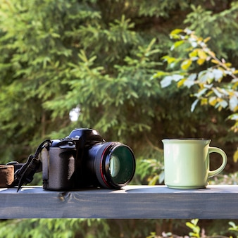 Front view camera anc cup of coffee in nature