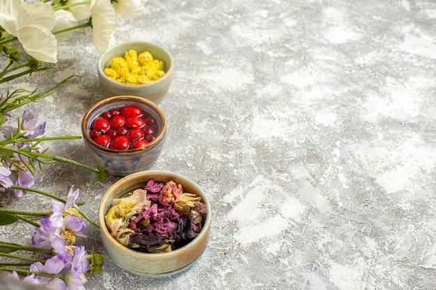 Caramelle e gelatina di vista frontale con i fiori sul fiore dolce della caramella di superficie bianca