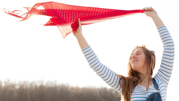 Front view of carefree woman holding scarf in the wind