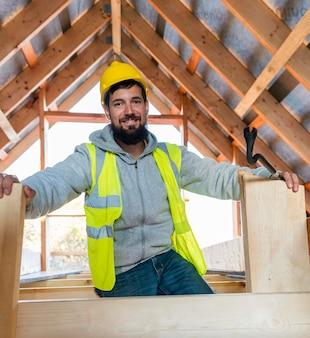 Вид спереди плотник человек сидит и улыбается