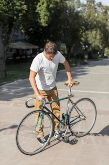 Maschio casuale di vista frontale che controlla la sua bicicletta