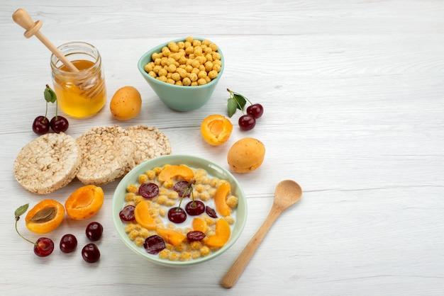 Вид спереди хлопья с молоком внутри синей тарелки с крекерами, фруктами и медом на белом столе пить молоко, молочные сливки, завтрак
