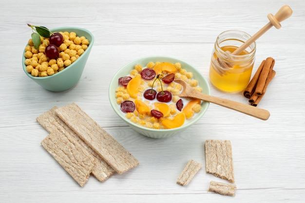 Вид спереди хлопья с молоком внутри тарелки с крекерами, корицей и медом на белом фоне пить молоко, молочные сливки, завтрак