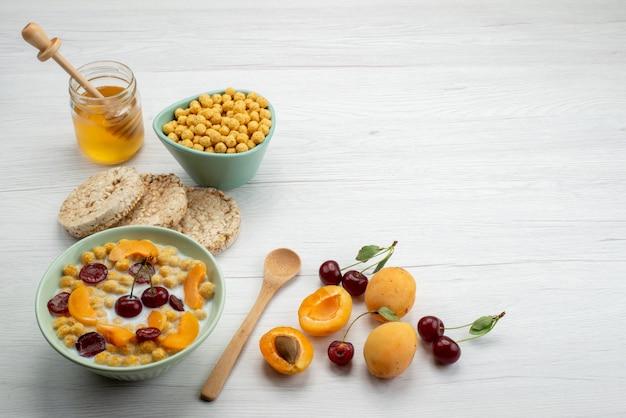 Вид спереди хлопья с молоком внутри тарелки с крекерами, фруктами и медом на белом фоне, пить молоко, молочные сливки, завтрак