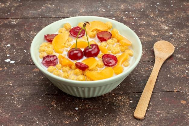 木製の茶色の背景のコーンフレークシリアル朝食に新鮮な果物とプレート内の牛乳と正面図シリアル