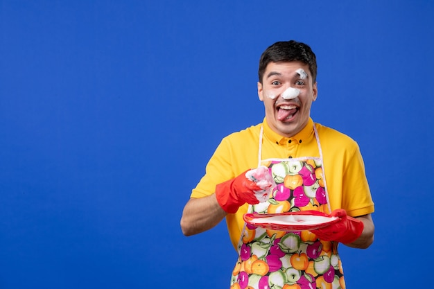 Front view cfunny cheerful housekeeper with foam on his face washing plate on blue space