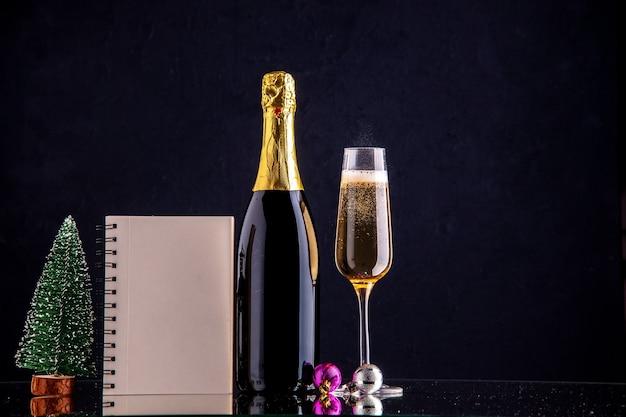 Vista frontale champagne in bottiglia e vetro mini taccuino albero di natale su superficie scura