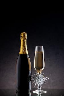 暗い表面の正面図のシャンパングラスのボトル