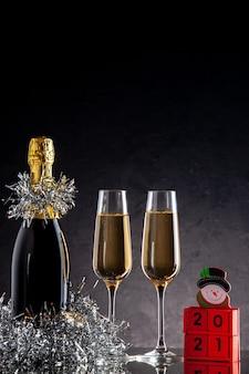 暗い表面にボトルとグラスの木製ブロックの正面のシャンパン