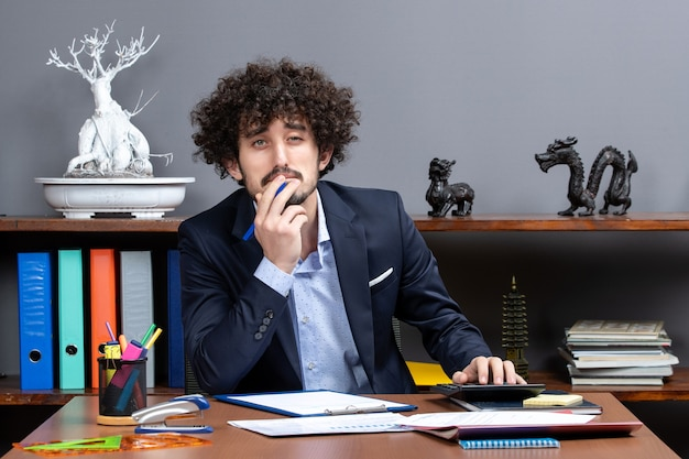 Front view charismatic young businessman sitting at desk in office